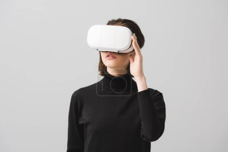 brunette young woman touching virtual reality headset isolated on grey