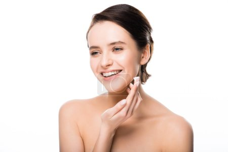 Photo for Cheerful woman applying face cream and smiling isolated on white - Royalty Free Image