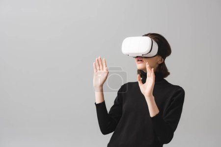 femme brune surprise portant un casque de réalité virtuelle tout en gesticulant isolé sur gris