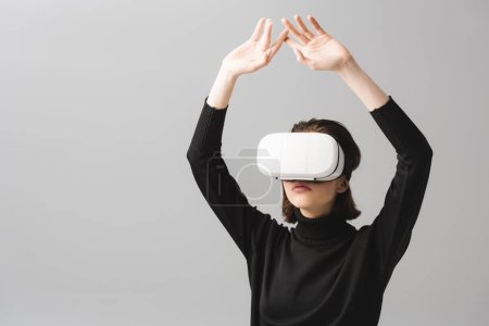 Photo for Brunette woman wearing virtual reality headset while standing with hands above head isolated on grey - Royalty Free Image
