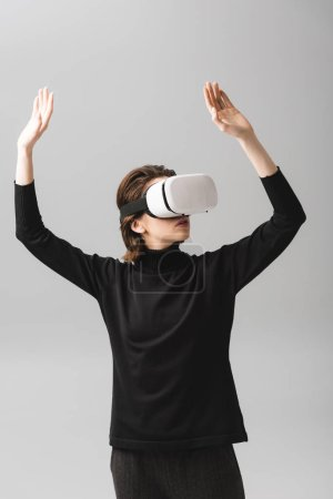 woman wearing virtual reality headset while standing with hands above head isolated on grey