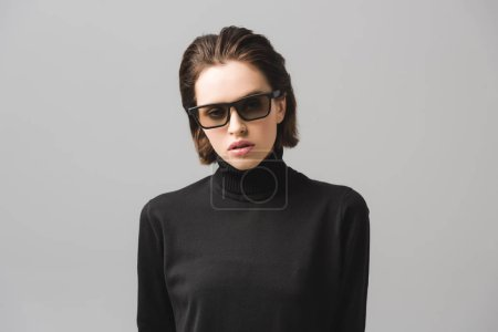 attractive young woman in black sweater and sunglasses isolated on grey