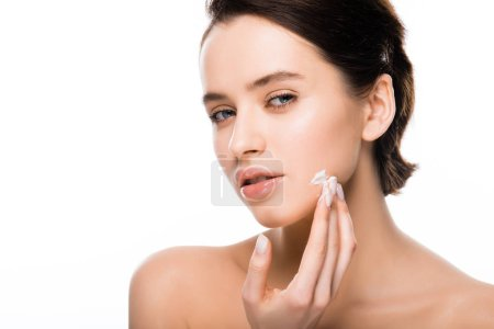 Photo for Young brunette woman applying face cream isolated on white - Royalty Free Image