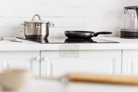 Photo for Selective focus of stainless saucepan and black frying pan on electric stove in kitchen - Royalty Free Image