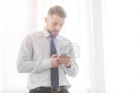 Foto de Guapo hombre barbudo en traje usando teléfono inteligente mientras está de pie en casa - Imagen libre de derechos