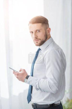 Foto de Guapo barbudo hombre de traje sosteniendo teléfono inteligente mientras mira a la cámara - Imagen libre de derechos