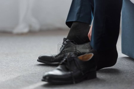 Photo for Cropped view of man wearing black shoe at home - Royalty Free Image