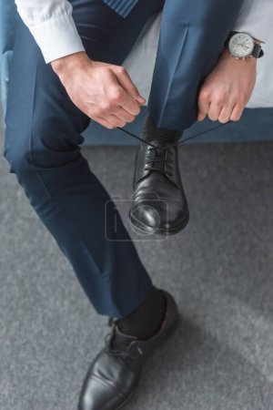 Photo for Cropped view of man tying shoelaces on black shoes at home - Royalty Free Image