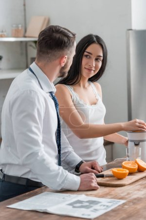Photo for Attractive brunette woman looking at man in suit while squeezing oranges in juicer - Royalty Free Image