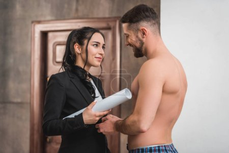Photo for Cheerful muscular and shirtless man looking at brunette young woman - Royalty Free Image