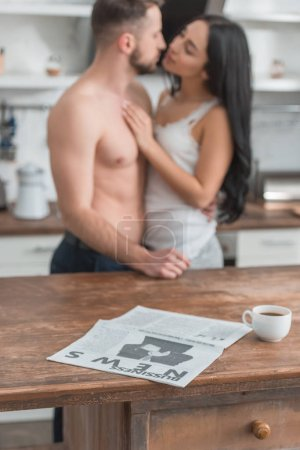 selective focus of business newspaper near cup of coffee and couple in kitchen