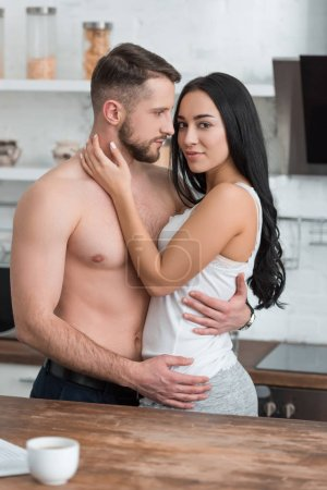 Photo for Attractive brunette woman hugging muscular and handsome boyfriend in kitchen - Royalty Free Image