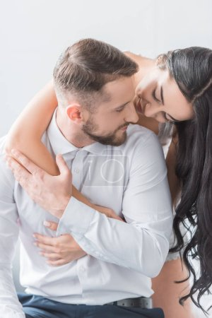 Photo for Cheerful girlfriend hugging bearded happy boyfriend at home - Royalty Free Image