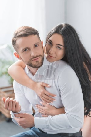 Photo for Happy girlfriend hugging bearded boyfriend in white shirt at home - Royalty Free Image
