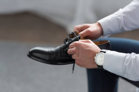 Photo for Cropped view of man with watch on hand holding black shoe - Royalty Free Image