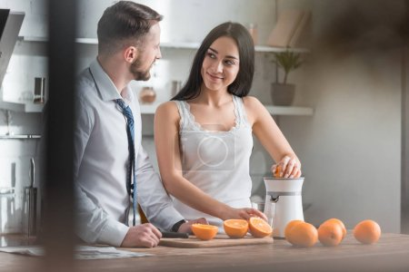 Photo for Happy brunette girl squeezing orange and looking at bearded man - Royalty Free Image