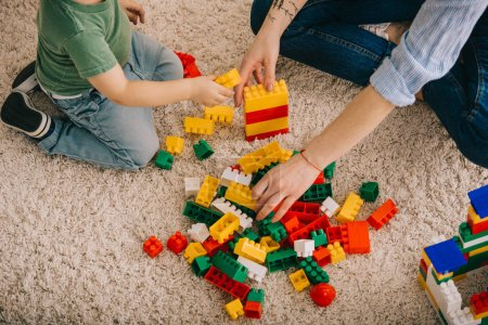 Photo for Cropped view of mom and son playing with toy blocks on carpet - Royalty Free Image