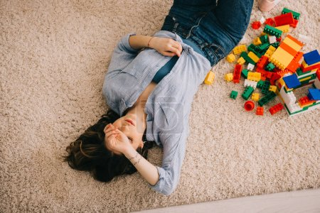 Photo for Overheaf view of tired woman lying on carpet with colorful toy blocks - Royalty Free Image