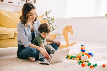 Photo pour Maman et fils s'asseyant sur le tapis et utilisant l'ordinateur portatif - image libre de droit