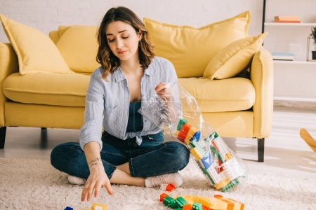 Photo for Tired woman in jeans sitting on carpet with toy blocks - Royalty Free Image