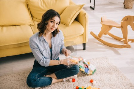 Foto de Woman with toy blocks sitting with crossed legs on carpet - Imagen libre de derechos