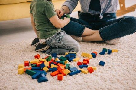 Photo pour Vue recadrée de la mère et du fils jouant avec des blocs de jouets sur le tapis - image libre de droit