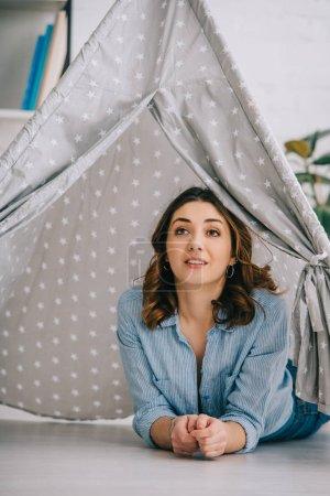 Photo pour Jeune femme inspirée allongée dans un wigwam gris à la maison - image libre de droit
