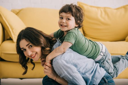 Photo for Smiling mother and son playing together near yellow sofa - Royalty Free Image