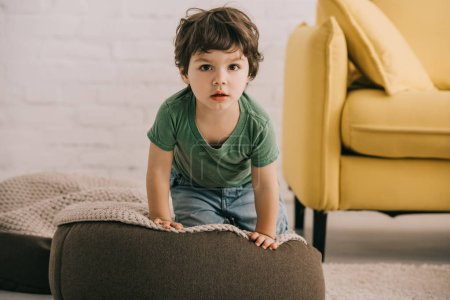 Photo for Front view of little boy in green t-shirt sitting on pouf - Royalty Free Image