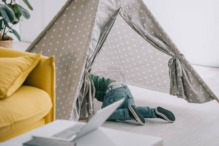 Photo for Little boy in jeans playing in grey wigwam in living room - Royalty Free Image