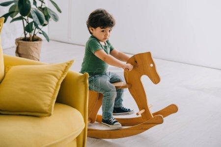 Photo pour Petit garçon mignon s'asseyant sur le cheval de bascule en bois dans la salle de séjour - image libre de droit