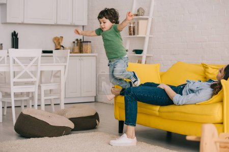 Photo for Kid having fun while tired mother lying on sofa - Royalty Free Image