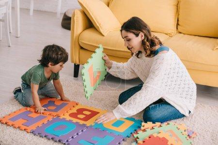 Photo pour Mère et fils jouant avec le tapis de puzzle d'alphabet sur le tapis - image libre de droit