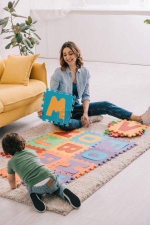 Photo pour Mère et gosse de sourire jouant avec le tapis de puzzle d'alphabet - image libre de droit