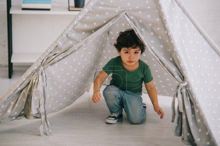 Photo pour Mignon enfant en jeans assis dans wigwam gris à la maison - image libre de droit
