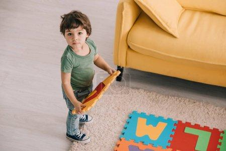 Photo pour Vue au-dessus de l'enfant mignon dans le t-shirt vert jouant avec le tapis de puzzle - image libre de droit