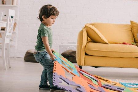 Photo pour Vue pleine longueur de l'enfant dans le t-shirt vert jouant avec le tapis de puzzle - image libre de droit