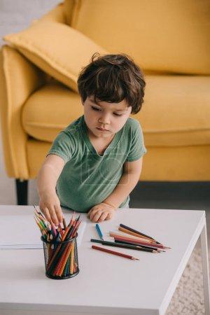 Photo pour Enfant dans le t-shirt vert avec des crayons de couleur et des papiers dans le salon - image libre de droit