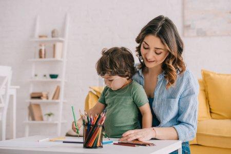 Photo pour Dessin de mère et de fils avec des crayons de couleur dans la salle de séjour - image libre de droit