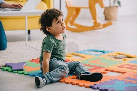 Photo pour Curieux enfant en jeans assis sur tapis puzzle avec des lettres - image libre de droit