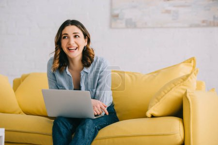 Photo for Smiling pretty freelancer sitting on yellow sofa with laptop - Royalty Free Image