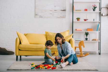 Photo pour Mother and son playing with lego on carpet in living room - image libre de droit