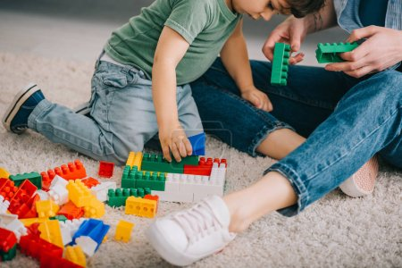 Photo for Cropped view of mother and son playing with lego on carpet in living room - Royalty Free Image