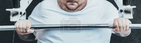 Photo for Panoramic shot of Overweight man training with barbell at gym - Royalty Free Image