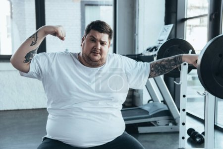 Photo for Overweight tattooed man sitting on bench, looking at camera and showing muscles at gym - Royalty Free Image
