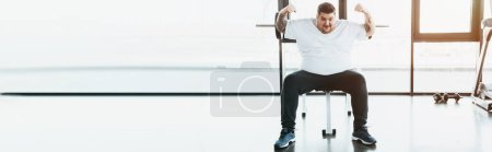 Photo for Panoramic shot of overweight tattooed man sitting on bench and showing muscles at gym - Royalty Free Image