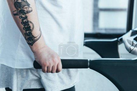 Photo pour Vue recadrée de l'homme tatoué de poids excessif fonctionnant sur le tapis roulant au centre sportif - image libre de droit