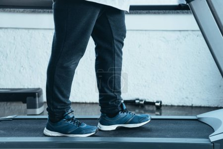 Photo pour Cropped view of overweight man in trainers running on treadmill at sports center - image libre de droit