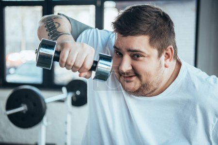 Photo for Smiling Overweight tattooed man Looking At Camera and exercising with dumbbell at sports center - Royalty Free Image