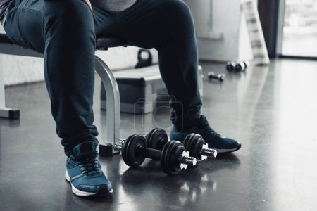 Photo for Cropped view of man in trainers sitting with dumbbells at sports center - Royalty Free Image